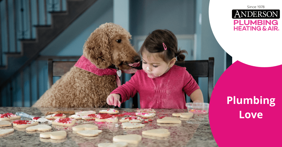 child sitting at a table with a dog making valentine's day cookies